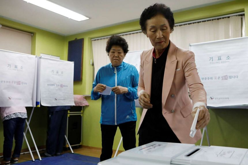 People cast their votes at a polling station during the presidential elections in Seoul, on May 9, 2017.