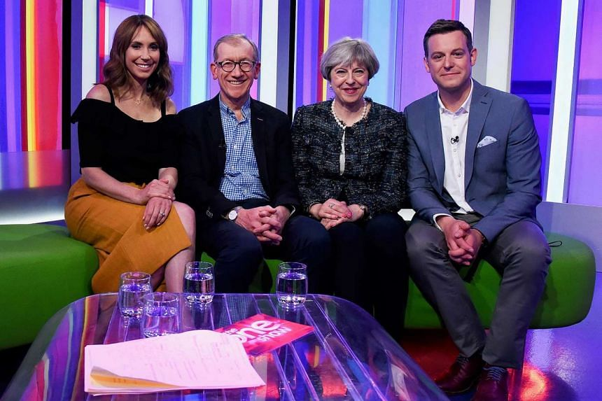 British Prime Minister Theresa May (2nd from right) and her husband Philip Jon May (2nd from left) as they pose for a photograph with the hosts of the BBC's The One Show, Matt Baker (right) and Alex Jones.