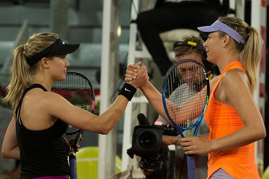 Eugenie Bouchard (left) and Maria Sharapova exchanging a handshake at the end of their Madrid Open second-round match on Monday. Bouchard won the game 7-5, 2-6, 6-4.