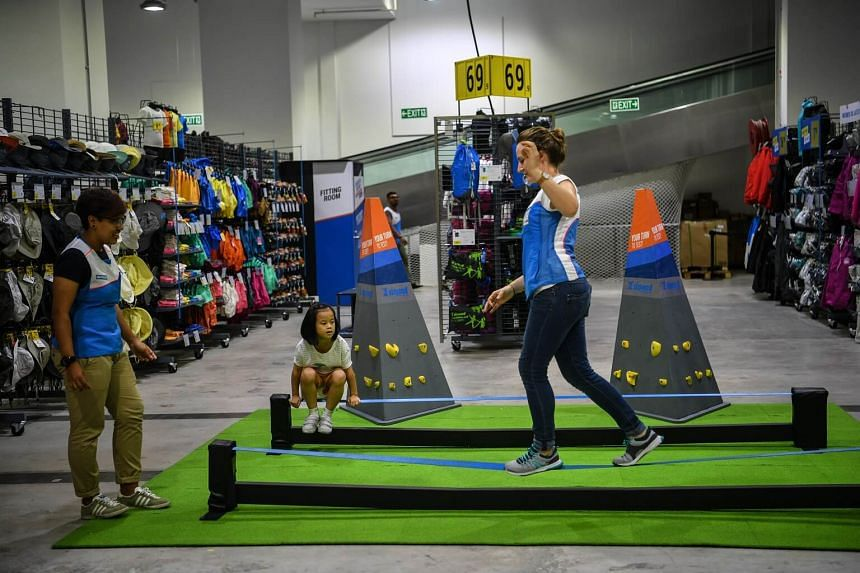 A Decathlon staff member walks along a slack line at the new store in Joo Koon on May 11, 2017.
