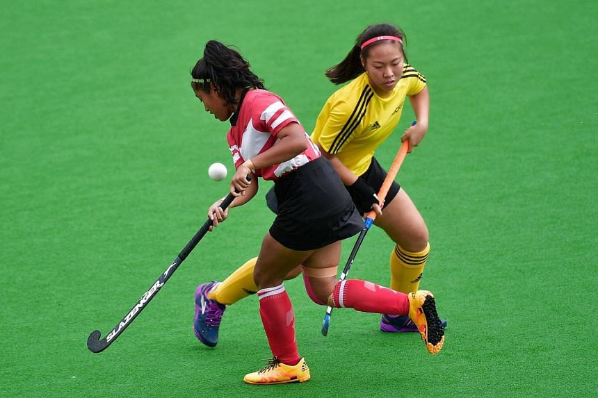 Millennial Institute's Diyana Khairunnisa (left) attempts to go past Victoria JC's Hilary Lau Xinyi during the A' Division girls Hockey Finals on May 11, 2017.