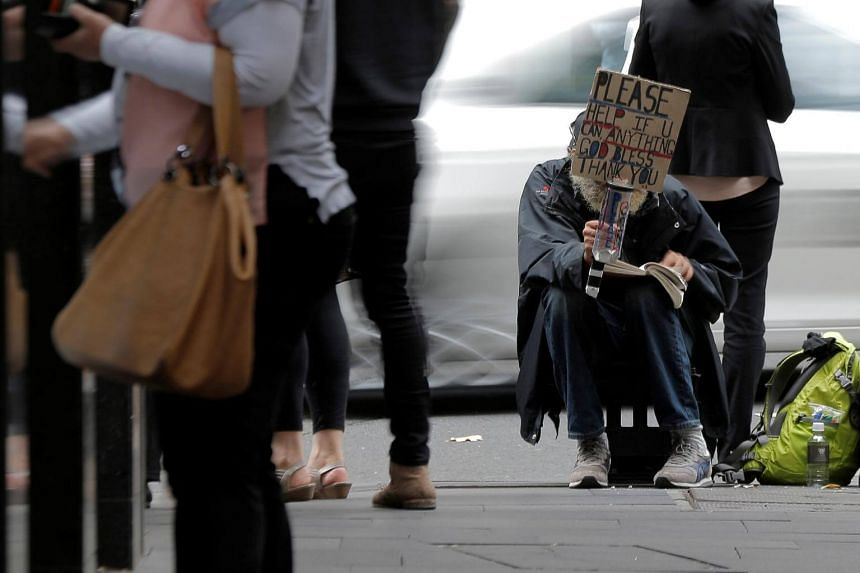 A man panhandles among office workers on the streets of Sydney, Australia, on May 4, 2017.
