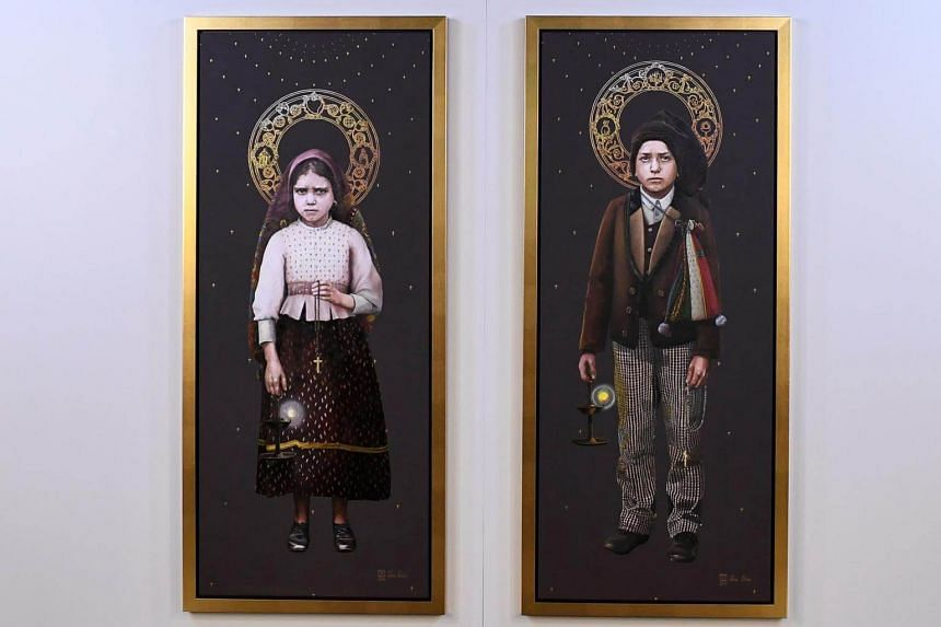 Two paintings by Silvia Patricio depicting Fatima's shepherds Jacinta (left) and Francisco Marto presented during a press conference at Fatima shrine in Fatima, central Portugal on May 8, 2017.