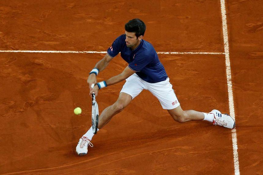 Djokovic returns the ball to Feliciano Lopez of Spain.
