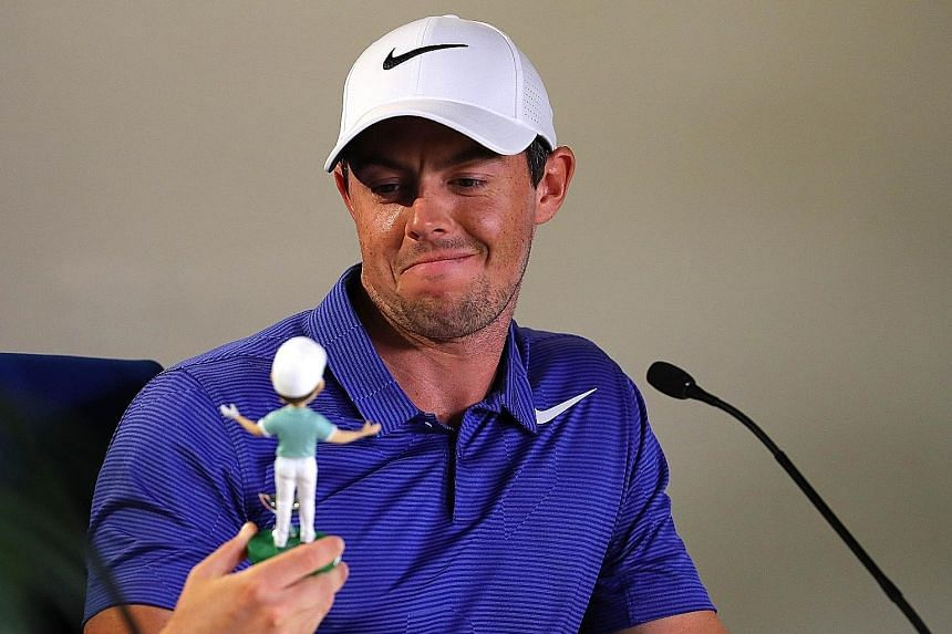 Rory McIlroy admiring a bobblehead doll version made in his likeness. The Northern Irishman hopes new gear will aid him in his first tournament since his layoff.