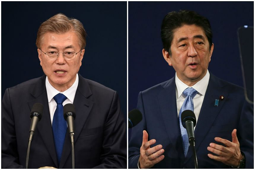 South Korean President Moon Jae In (left) and Japanese Prime Minister Shinzo Abe have agreed to hold a bilateral summit meeting at an early date.