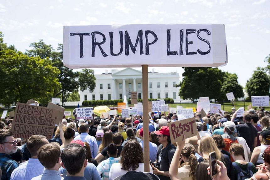 Demonstrators protesting outside the White House after US President Donald Trump fired James Comey.