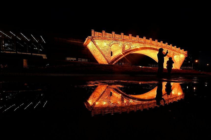 """People take pictures in front of a """"Golden Bridge on Silk Road"""" installation, set up ahead of the Belt and Road Forum, in Beijing, China on May 11, 2017."""