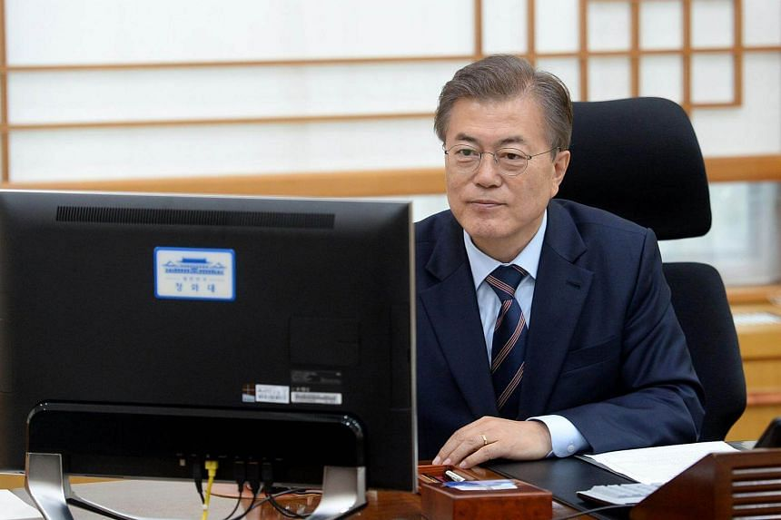 South Korea's new President Moon Jae In electronically puts his signature to an order to scrap state-issued school history textbooks in his office at the presidential Blue House, on May 12, 2017.