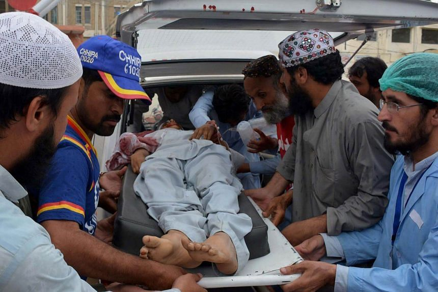 Pakistani volunteers move an injured blast victim to a hospital in Quetta on May 12, 2017 following a powerful explosion in Mastung district.