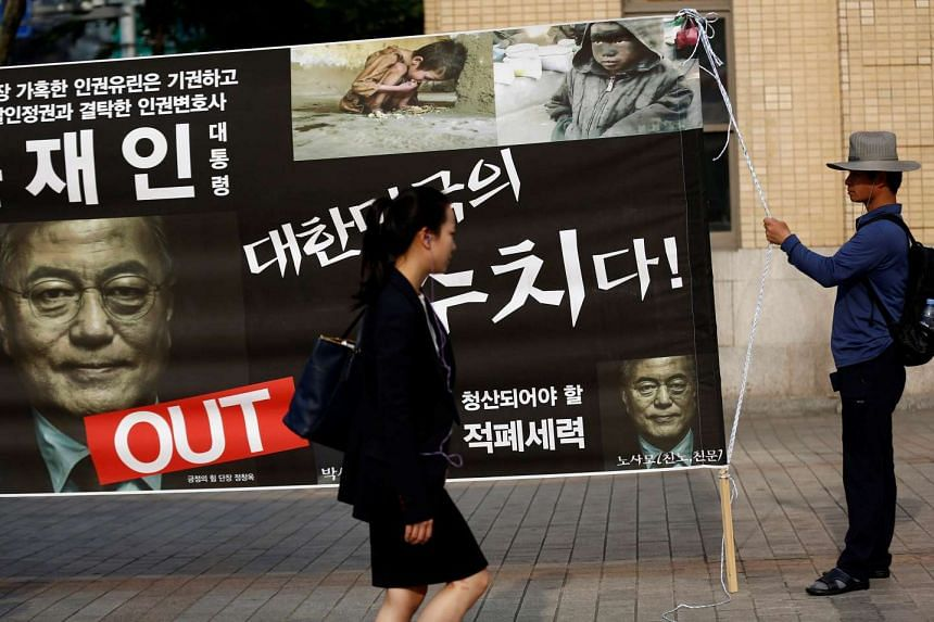 An activist holds a placard opposing new South Korean President Moon Jae In's policy on North Korea.