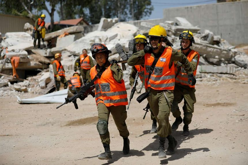 Arpon (front, left) helps evacuate her comrade during a drill at Tzrifin military base in central Israel.