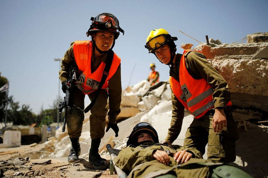 Arpon (left) helps evacuate her comrade during a drill at Tzrifin military base in central Israel.