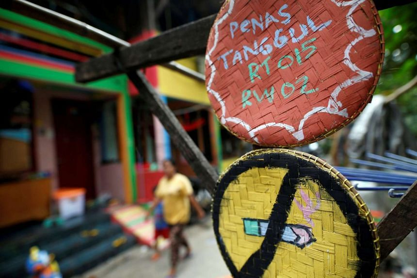 A woman and child walk near a no smoking sign hanging in a poor riverside neighborhood where locals have recently painted their homes in bright colours to encourage residents to stop smoking and promote a smoke-free environment in Penas Tanggul, East