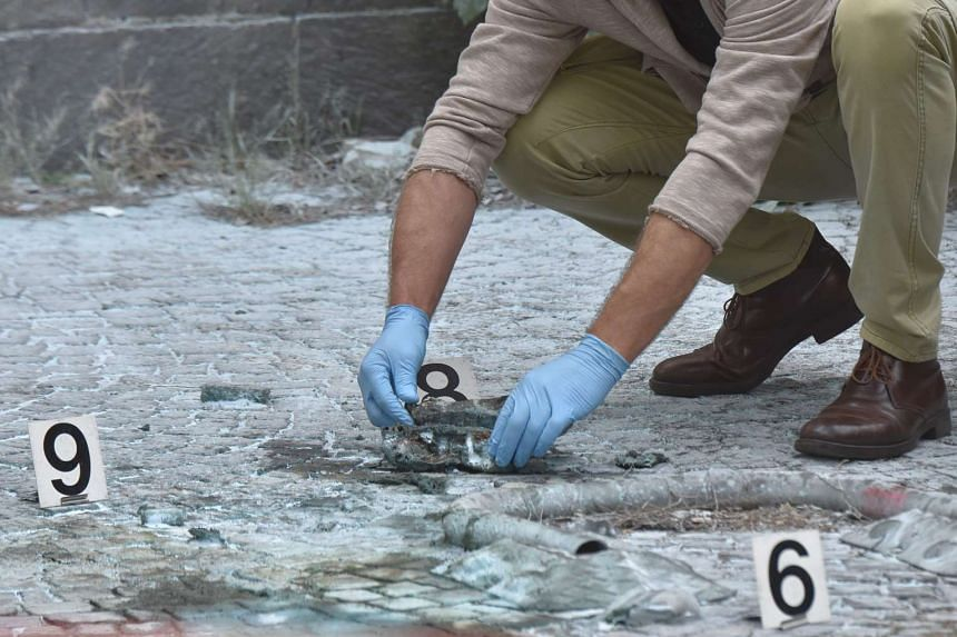 Scientific police works on the site of the explosion of a rudimentary bomb placed between two cars near a post office in Via Marmorata, on May 12, 2017 in Rome.