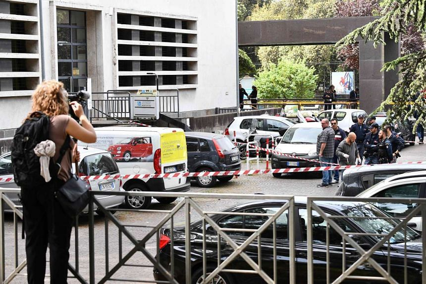 Police works on the site of the explosion of a rudimentary bomb placed between two cars near a post office in Via Marmorata, on May 12, 2017.
