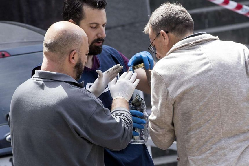 Police experts search for evidence at the site of an explosion outside a post office in Rome, Italy on May 12, 2017.