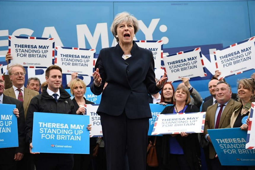 May addresses supporters and members of the media in front of the Conservative party's election campaign bus.