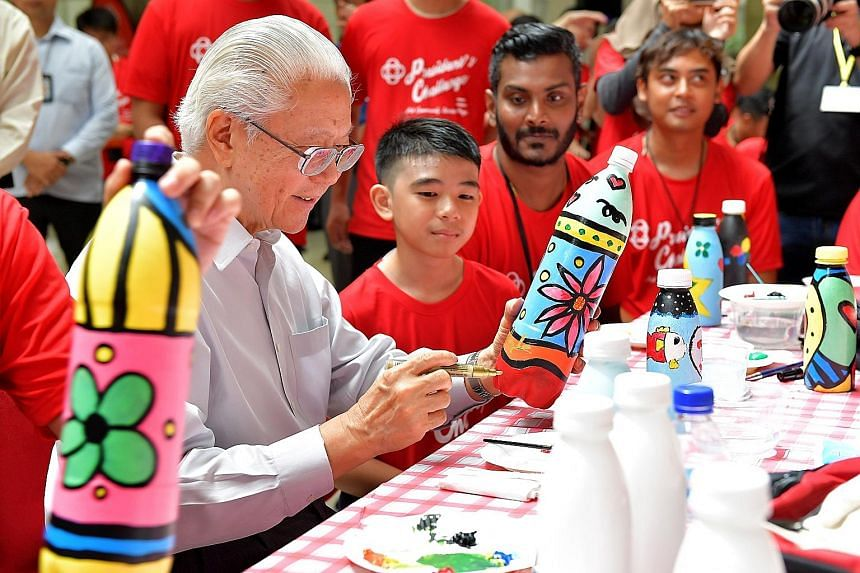 Meridian Secondary School student Adry Fariqaeen, 12, observing President Tony Tan Keng Yam at a bottle art and bag painting workshop at the People's Association (PA) headquarters in King George's Avenue yesterday. At the event, PA chief executive di