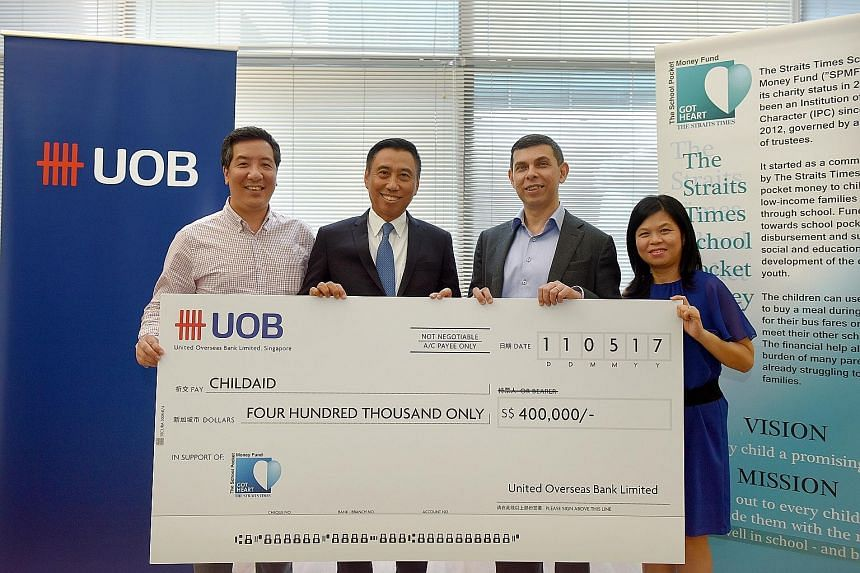 The Straits Times School Pocket Money Fund (STSPMF) received a $400,000 boost from the United Overseas Bank yesterday, from funds raised through its clients at an annual Chinese New Year dinner in February. Mr Eric Tham (second from left), managing d