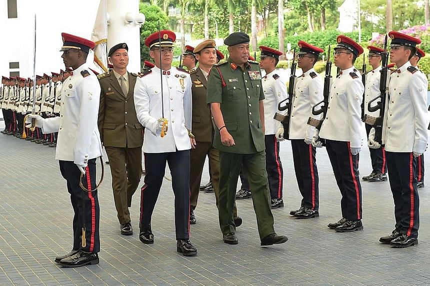 The Chief of the Malaysian Armed Forces, General Raja Mohamed Affandi Raja Mohamed Noor, inspecting a guard of honour at the Ministry of Defence yesterday as part of a three-day introductory trip to Singapore. He also met Defence Minister Ng Eng Hen