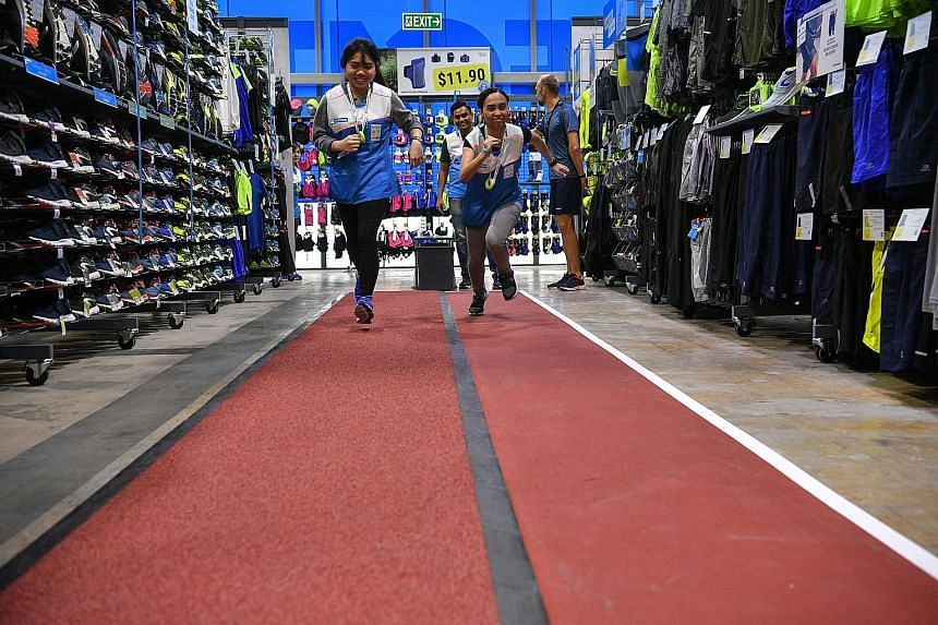 """Decathlon staff members putting their track shoes to use at the in-store running track in its latest Joo Koon outlet yesterday. The track is one of the """"experience zones"""" available for the use of its patrons at the 4,000 sq m outlet, the biggest of t"""