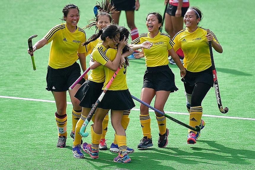 Klara Chong (third from left) embraces a team-mate in jubilation after scoring the golden goal to help Victoria Junior College claim their 15th straight A Division girls' hockey championship. Below: Raffles Institution's match winner Ramalingam Gouth