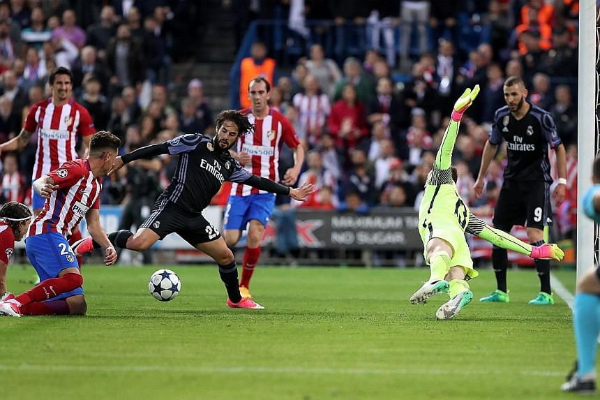 Real Madrid's Isco shoots past Atletico Madrid 'keeper Jan Oblak, after he could only parry a Toni Kroos shot into the Spaniard's path. The away goal sealed Atletico's fourth straight exit at Real's hands.