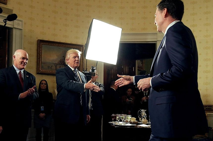 President Donald Trump and former FBI director James Comey in a January photo. Sources say Mr Trump grew increasingly agitated with Mr Comey's focus on the probe into Russia's links with the Trump campaign.