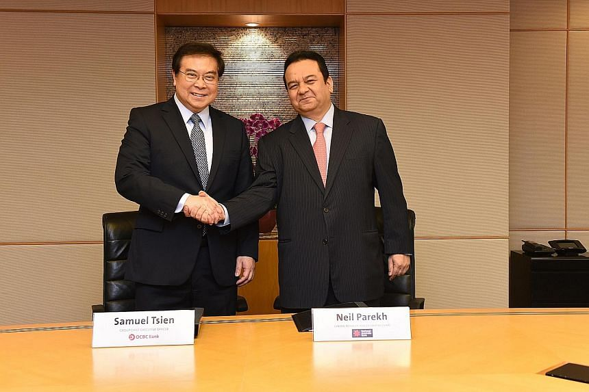 OCBC chief executive Samuel Tsien with National Australia Bank's general manager for Asia (ex-Greater China) Neil Parekh. OCBC's latest acquisition comes with a mortgage portfolio worth about US$1.7 billion of mainly residential mortgages, and a depo