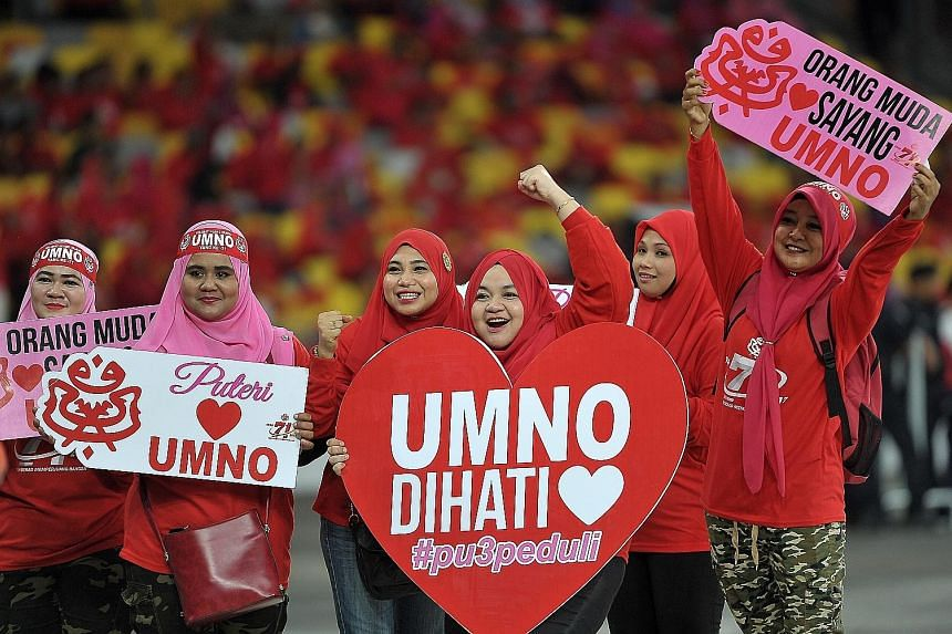 Umno members from Kulim, Kedah, holding up the party flag yesterday outside the Bukit Jalil National Stadium, which was filled with more than 120,000 people including members of the young women's wing, Puteri Umno (above, right), who gathered at the