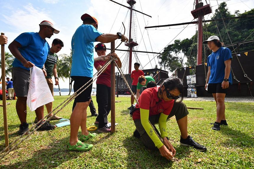 Participants constructing a flag pole with limited resources to raise a flag.