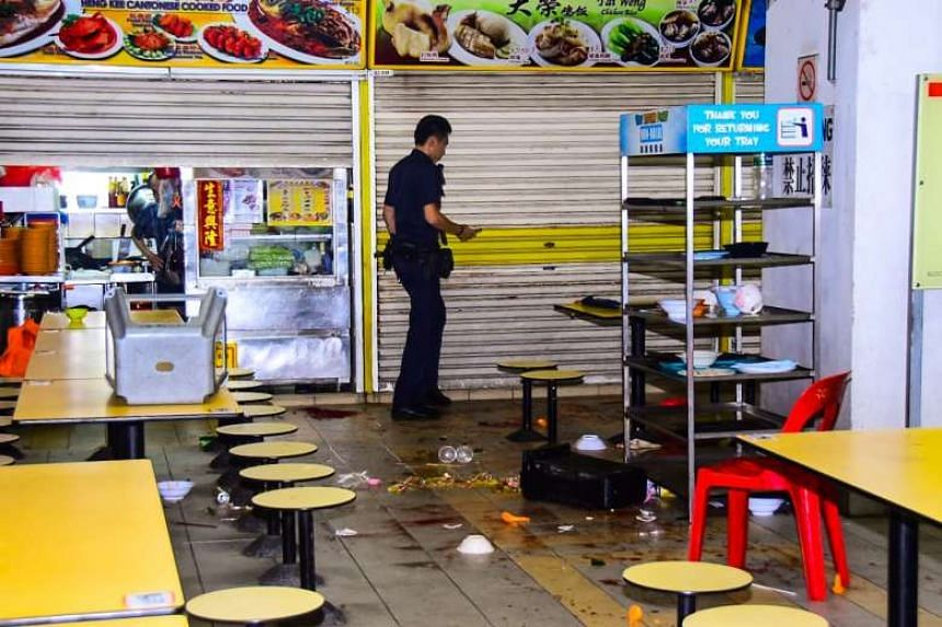 Two men were injured in the brawl, which left crockery, beer bottles, and chairs scattered on the floor of the food centre.