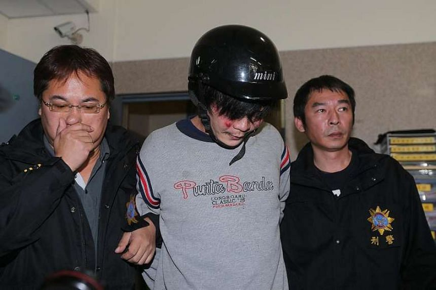 Police escorting the man (centre) who allegedly decapitated the four-year-old girl on a street in Taipei.
