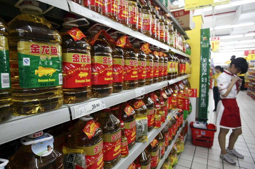 Bottles of Wilmar International's Arawana brand cooking oil sit on a shelf at a supermarket in Shanghai, China, on Friday, Aug. 14, 2009. PHOTO: BLOOMBERG
