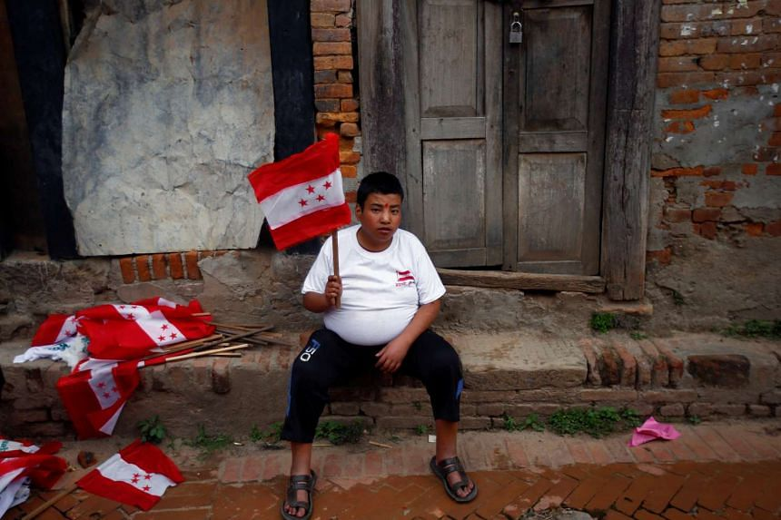 A man holding a party flag sits along a street of Bhaktapur, Nepal, on May 11, 2017.