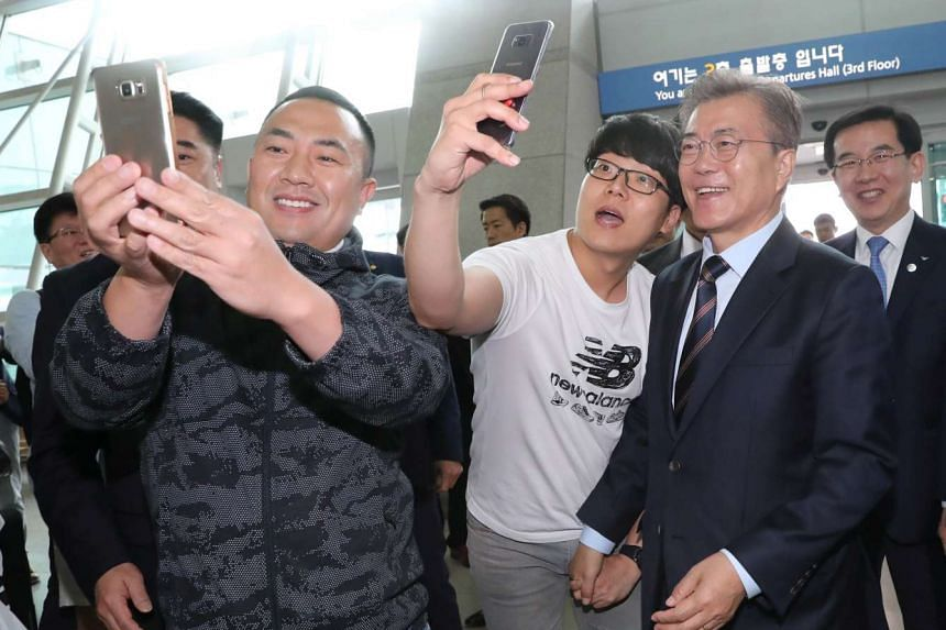 Moon Jae-in poses for selfies with visitors as he visits Incheon International Airport, May 12, 2017.