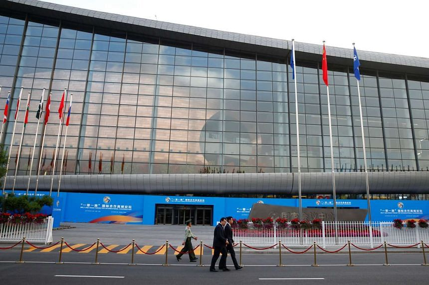 People walk past the China National Convention Center, the venue of the upcoming Belt and Road Forum on, May 12, 2017.