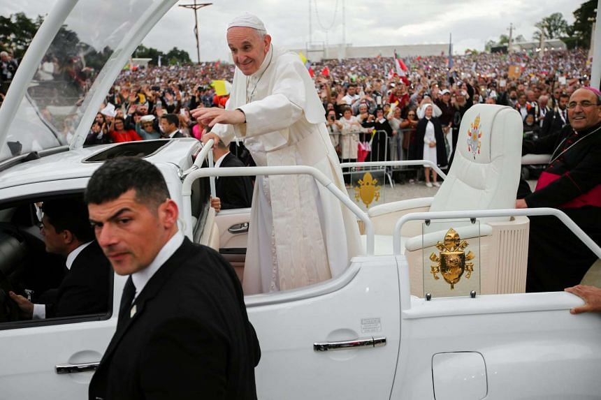 Pope Francis  waves to devotees from inside the popemobile.