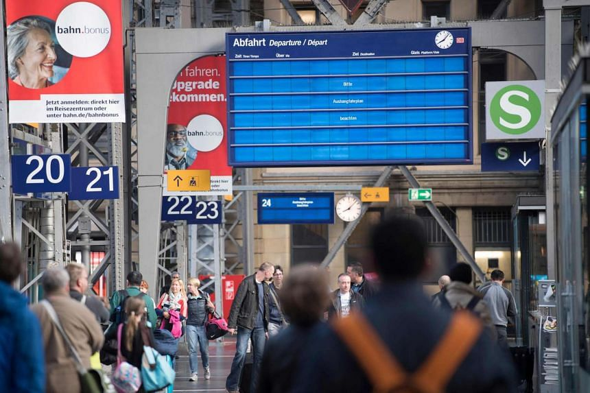 An electronic display calls on travellers to watch the analogue timetable at the main railway station in Frankfurt am Main, western Germany, on May 13, 2017.