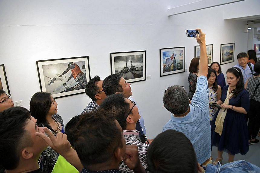 Visitors taking a wefie at an exhibition showcasing frame prints from the photo book, By Day & By Night: Missions Of RSS Sovereignty, which depicts the daily lives of the last crew of the Singapore navy patrol vessel.