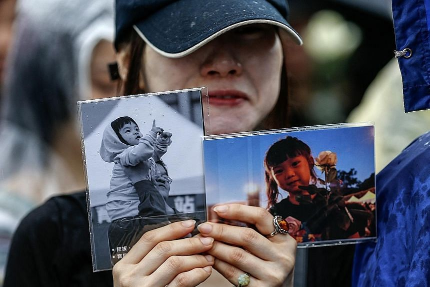 A protester holding photos of the four-year-old victim in April last year. Wang Ching-yu killed her on a Taipei street in front of her mother.