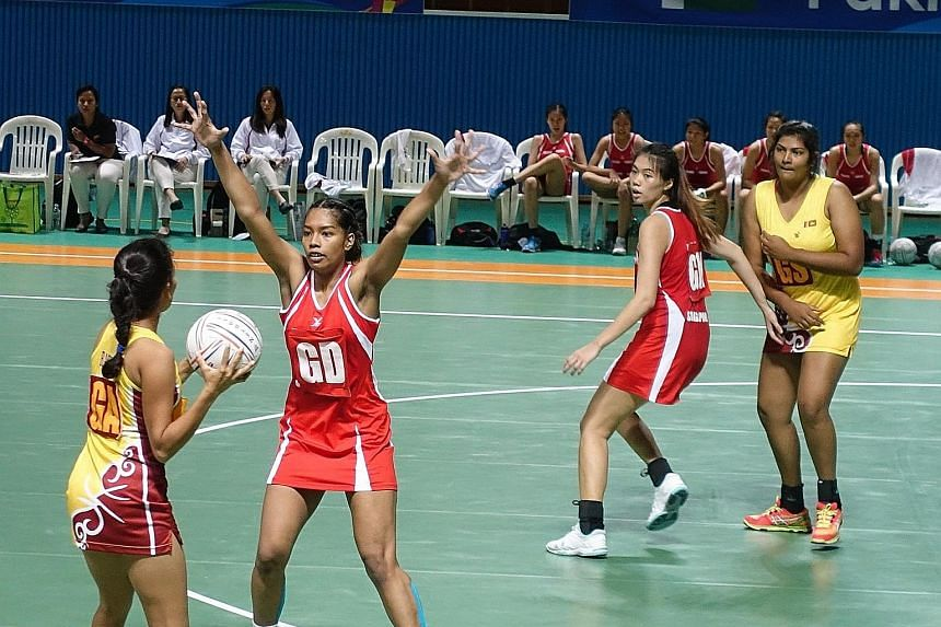 Singapore's Under-21 co-captain Aqilah Andin (above, second from left) defends during their Asian Youth Netball Championship's semi-final against Sri Lanka as team-mate Joanna Toh assesses the situation. Singapore won 58-32, and will face Malaysia in