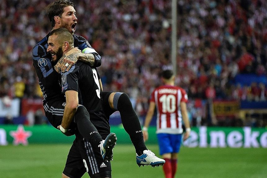Real Madrid forward Karim Benzema lifts team-mate Sergio Ramos off his feet as they celebrate their side's goal against Atletico Madrid in the Champions League semi-final second leg. Isco grabbed the away goal as Real progressed 4-2 on aggregate.