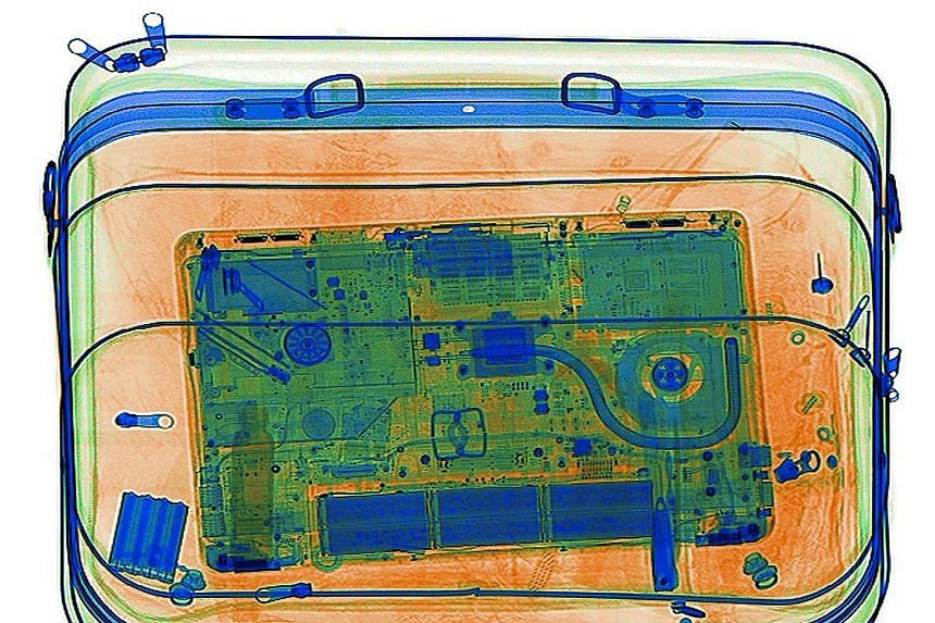 A laptop being screened by an X-ray scanner. US airlines are urging alternative solutions to the government's ban on electronic devices as part of carry-on luggage on flights to the US from certain countries.