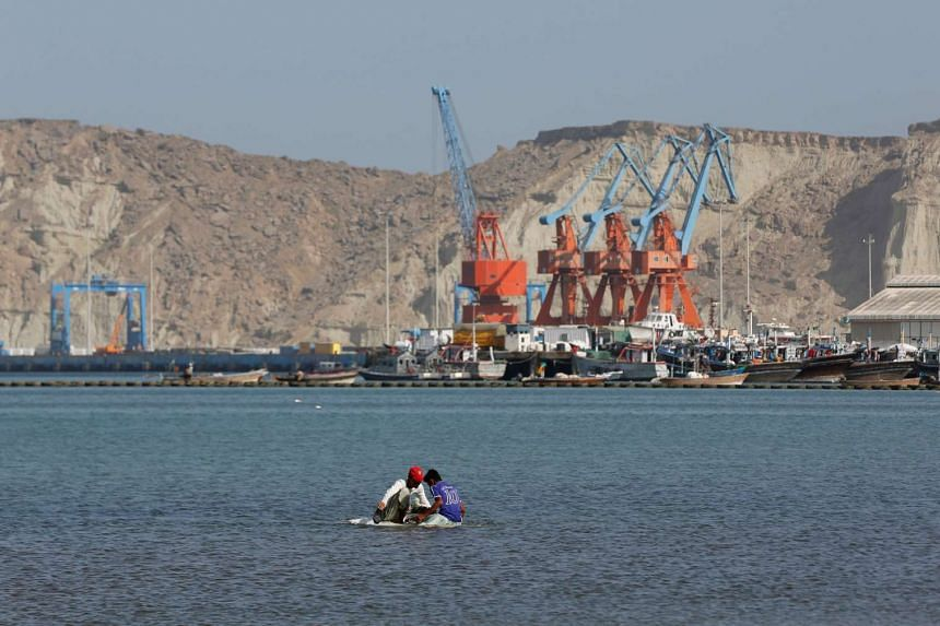 Boys sit on a piece of styrofoam sheet as they search for crabs in front of the Gwadar port, Pakistan on April 11, 2017.