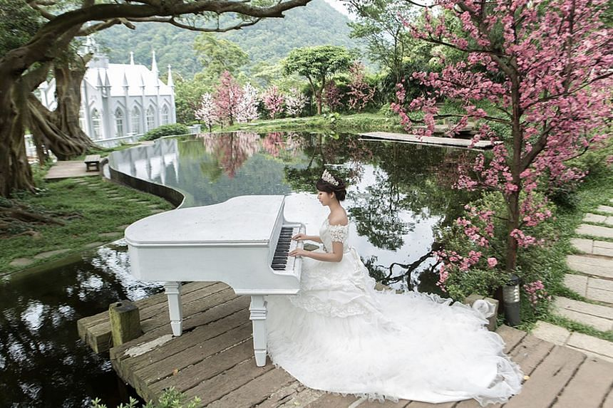 Ms Chen posing beside a lake in a wedding dress.