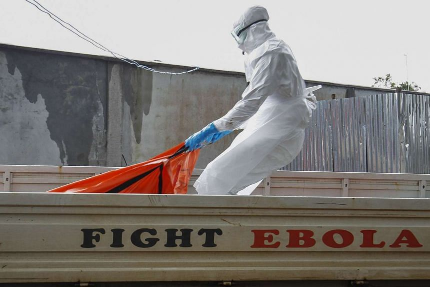 A Liberian health worker in a burial squad drags an Ebola victim's body for cremation from the ELWA treatment center in Monrovia, Liberia, on Oct 13, 2014.