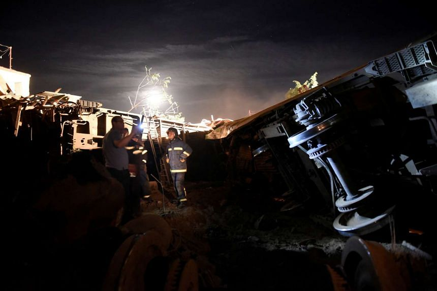 Firefighters work next to parts of a train that derailed and crashed, during a rescue operation in the town of Adendro in northern Greece on May 13, 2017.