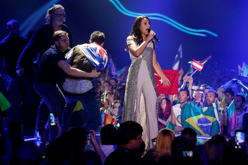 Ukraine's Jamala performs a song as security detain a fan during the grand final of the Eurovision Song Contest 2017 on May 14, 2017.
